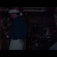 A close up of Old Saint Nick buying a drink.